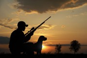 a hunter and a dog at sunset