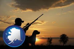 alaska map icon and a hunter and a dog at sunset