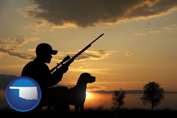a hunter and a dog at sunset - with Oklahoma icon