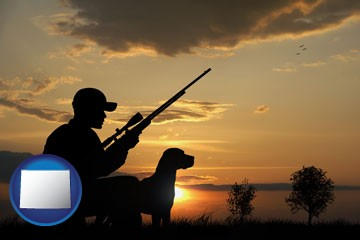 a hunter and a dog at sunset - with Wyoming icon